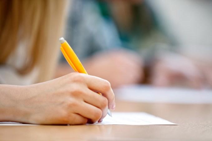 Estudante escrevendo em prova