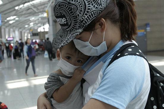 Um modo de tentar se proteger do contágio é a utilização de máscaras de proteção descartáveis. A imagem mostra uma mãe com seu filho no Aeroporto Internacional de Incheon, na Coreia do Sul. (Imagem: Chung Sung-Jun/Getty Images)