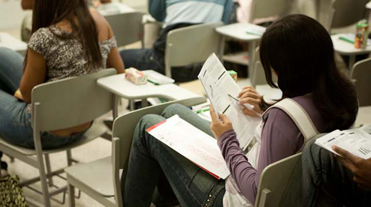 Garota lê enunciado de prova