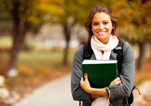 garota-sorrindo-jardim-segurando-cadernos.jpg