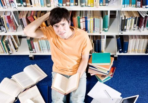 garoto-confuso-livros-espalhados.jpg