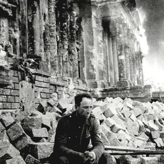 Um soldado alemão senta sobre as ruínas do Palácio do Reichstag no dia 9 de maio de 1945. (Créditos: Laski Diffusion/Getty Images)