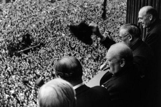 O Primeiro Ministro da Inglaterra Winston Churchill acena para a multidão reunida em frente ao Palácio Whitehall no dia 8 de maio de 1945, o Dia da Vitória na Europa. (Créditos: Keystone/Getty Images)