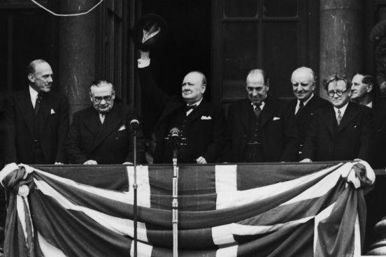 O Primeiro Ministro da Inglaterra Winston Churchill discursa para a multidão reunida ao redor do Ministério da Saúde em Whitehall no dia 8 de maio de 1945. (Créditos: Central Press/Hulton Archive/Getty Images)