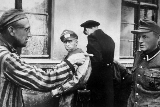 Um trabalhador escravo russo que estava entre os presos libertados pelo exército americano aponta para um guarda nazista que havia espancado brutalmente os prisioneiros. (Créditos: Harold M Roberts/Getty Images)