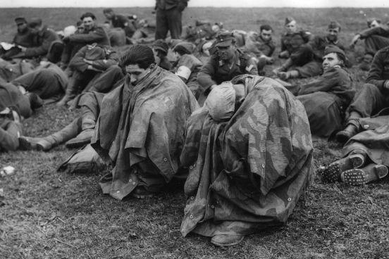 Cansados e desolados, prisioneiros de guerra alemães se abrigam debaixo de capas impermeáveis após serem capturados nas margens do rio Reno. (Créditos: Fred Ramage/Keystone/Getty Images)