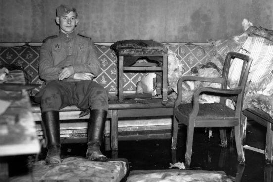 Um soldado russo senta-se sobre o sofá onde se acredita que Adolf Hitler se suicidou em seu abrigo subterrâneo, o Führerbunker, em Berlim. (Foto: Fred Ramage / Keystone / Getty Images)