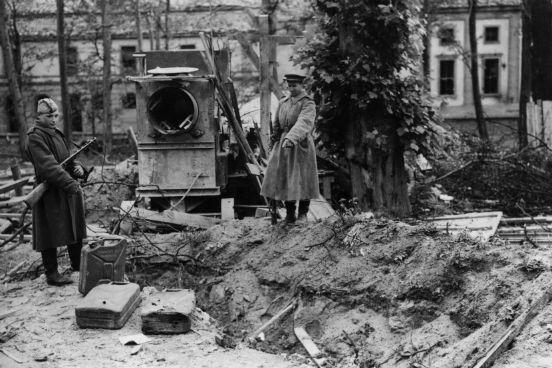 Dois soldados russos apontam para o que seria o túmulo de Hitler nos fundos do seu bunker em Berlim. Ao lado deles estão latas de gasolina. (Créditos: Fred Ramage/Keystone/Getty Images)