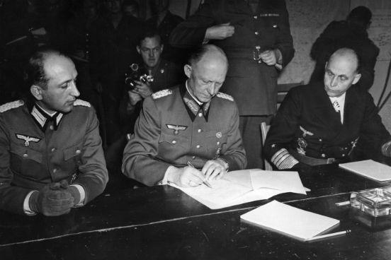 O General Alfred Jodl, conselheiro militar de Hitler e chefe da equipe de operações do Alto Comando Germânico (ao centro) assina o documento de rendição das forças armadas alemãs em Reims, na sede do General Eisenhower. (Foto: Keystone / Getty Images)