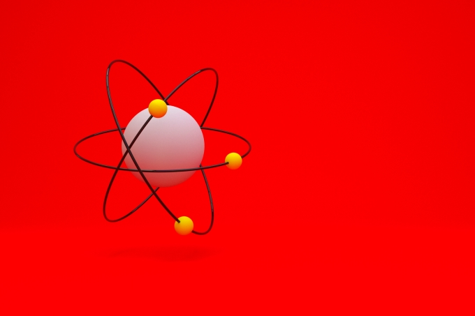 Model of atom with shadow on red background, 3D