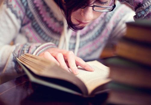 menina-leitura-pilha-livros.jpg