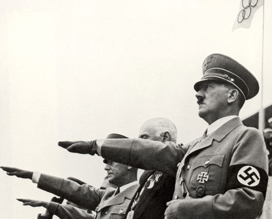 Em Berlim, Adolf Hitler quis mostrar a superioridade ariana no esporte, mas os negros americanos roubam a cena e ganharam várias medalhas. Há um mito de que Adolf Hitler teria se recusado a cumprimentá-los. Na foto: Hitler faz a saudação nazista na abertura do evento. Crédito: Getty Images