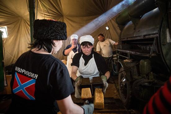 Rebeldes pró-Rússia fazem pão para entregar a civis como a ajuda humanitária em Chornukyne, pequena aldeia do leste Ucrânia controlada por eles desde o começo do ano. A região foi seriamente danificada pelos combates entre o exército e esses ucranianos pró-Rússia. (Foto: Andrew Burton / Getty Images)
