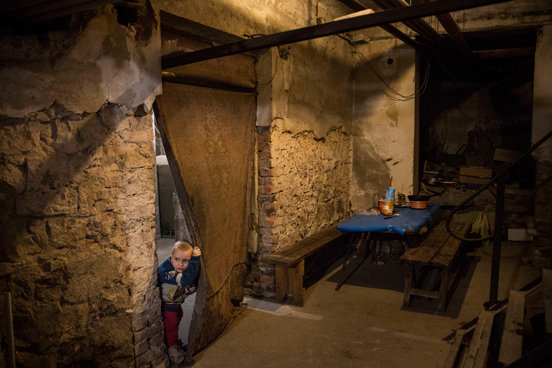 As crianças Pavel Makeev, de cinco anos de idade, e Raya Makeeva, de sete, esperam o almoço ficar pronto no porão de um centro cultural no leste da Ucrânia, onde vivem atualmente. A região tem sido fortemente atacada por forças ucranianas, obrigando a maioria dos moradores a fugir ou a se esconder em lugares como esse. As pessoas têm vivido no espaço desde junho de 2014. (Foto: Andrew Burton / Getty Images)