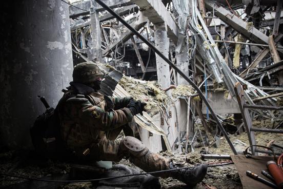 Um rebelde pró-Rússia descansa enquanto monitora soldados ucranianos prisioneiros de guerra que foram forçados a buscar por corpos no meio dos destroços do aeroporto. (Foto: Andrew Burton / Getty Images)