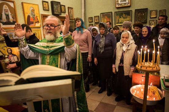 Grupo se reúne para orações em escritório de igreja ortodoxa russa em Donetsk, na Ucrânia. O salão principal da igreja foi destruído por um bombardeio em 2014, forçando a congregação a se reunir em um espaço improvisado desde então. (Foto: Andrew Burton / Getty Images).