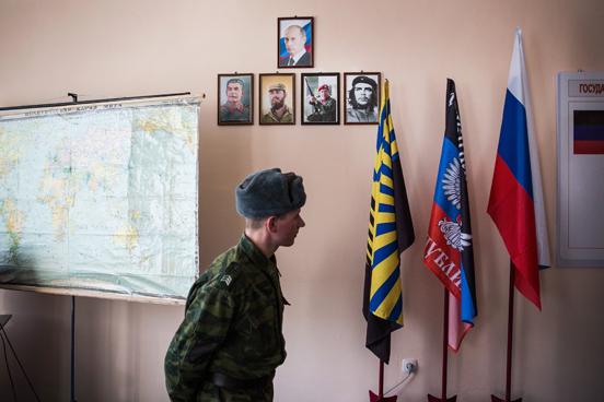 Um rebelde pró-Rússia passa por retratos do presidente russo Vladmir Putin e dos líderes pró-comunismo na sede do Batalhão Kalmius, em Donetsk, Ucrânia. (Foto: Andrew Burton / Getty Images)