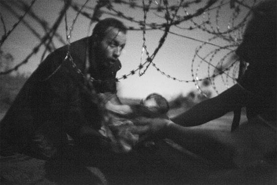 A grande vencedora deste ano na premiação da WWP é esta imagem que mostra um homem passando um bebê para uma outra pessoa por baixo de uma cerca de arame farpado. A foto foi registrada pelo australiano Warren Richardson no dia 28 de agosto de 2015, na fronteira entre a Sérvia e a Hungria. Segundo o fotógrafo, que acampou com os refugiados, essas pessoas tentavam chegar na Hungria antes que a cerca de segurança estivesse concluída (Crédito foto: Warren Richardson/World Press Photo 2016).