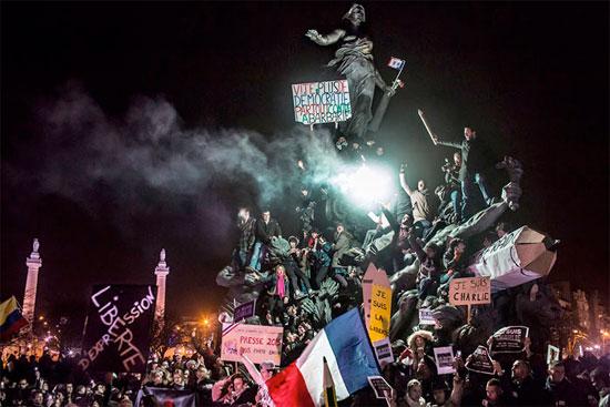 Manifestantes em torno da escultura O Triunfo da República, em Paris, protestam contra o terrorismo após os atentados contra o jornal satírico Charlie Hebdo em janeiro de 2015 (Crédito foto: Corentin Fohlen/World Press Photo 2016).