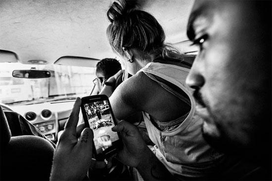 Líder do coletivo independente de mídia Papo Reto recebe uma imagem pelo celular que mostra um taxista morto pela polícia. O Papo Reto foi criado por um grupo de jovens do Morro do Alemão para divulgar reportagens de sua comunidade (Crédito foto: Sebastián Liste/Noor).