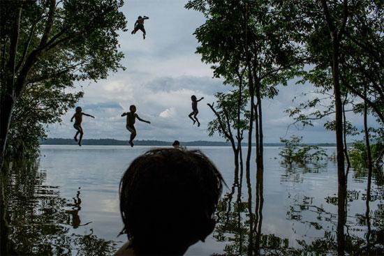 Crianças do grupo indígena Mundurucu brincam no Rio Tapajós, em Itaituba (PA). Os mundurucus vivem em vilarejos, cuja área deve ser inundada devido à construção da usina hidrelétrica São Luiz do Tapajós (Crédito foto: Mauricio Lima/Al Jazeera America).