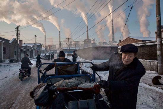 Homens carregam um triciclo em região próxima à usina de carvão em Shanxi, na China. O país é responsável por quase um terço de todo o dióxido de carbono emitido no planeta. O uso do carvão para a geração de energia é uma das principais causas do aquecimento global (Crédito foto: Kevin Frayer/Getty Images).