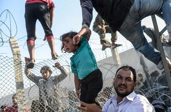 Refugiado sírio segura uma garota, enquanto outras pessoas tentam escalar a cerca de segurança para chegar até o campo de refugiados em Akçakale, na Turquia. Desde que o conflito na Síria começou, em 2011, quase 2 milhões de sírios fugiram para a Turquia (Crédito foto: Bulent Kilic/Agence France Presse).