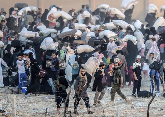A imagem mostra, em primeiro plano, membros do grupo extremista Estado Islâmico conduzindo dezenas de sírios de volta para as suas cidades. Essas pessoas tentavam cruzar a fronteira com a Turquia para chegar ao campo de refugiados em Akçakale, mas foram impedidas pelos terroristas (Crédito foto: Bulent Kilic/Agence France Presse).