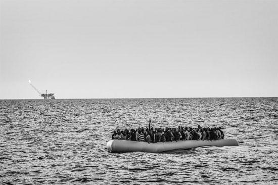 Um bote de borracha conduzindo dezenas de migrantes tenta cruzar o Mar Mediterrâneo para chegar da Líbia até a Itália (Crédito foto: Francesco Zizola/Noor).