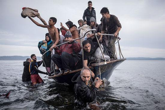 Pequena embarcação com refugiados chega à vila de Skala, na ilha de Lesbos, na Grécia (Crédito foto: Sergey Ponomarev/The New York Times).