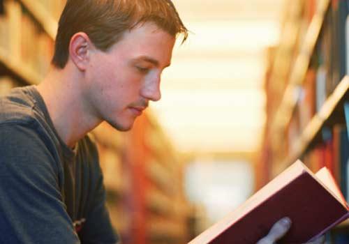 aluno-lendo-livro-biblioteca