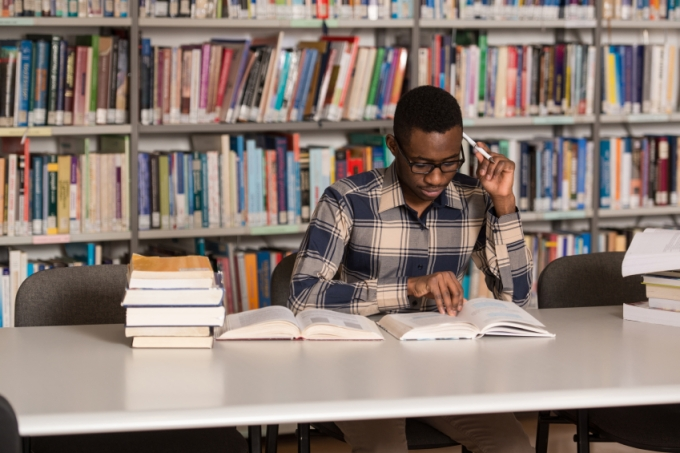 African Man Studying In A Library