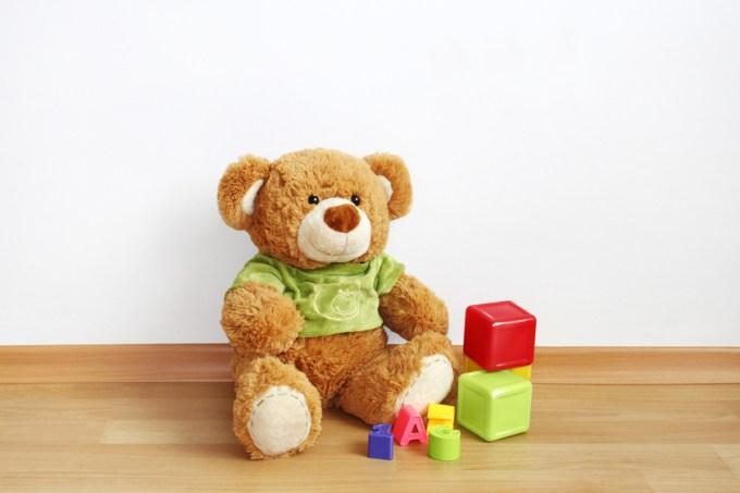 Teddy bear with cubes on laminate floor