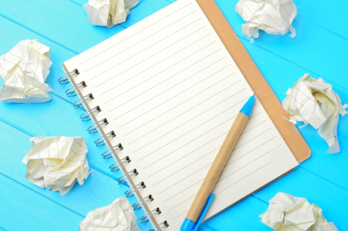 Empty notebook and crumpled paper
