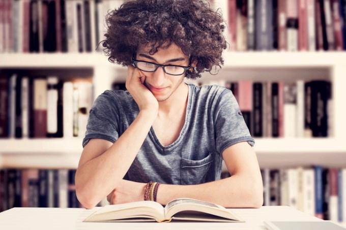 Jovem estudante lendo na biblioteca