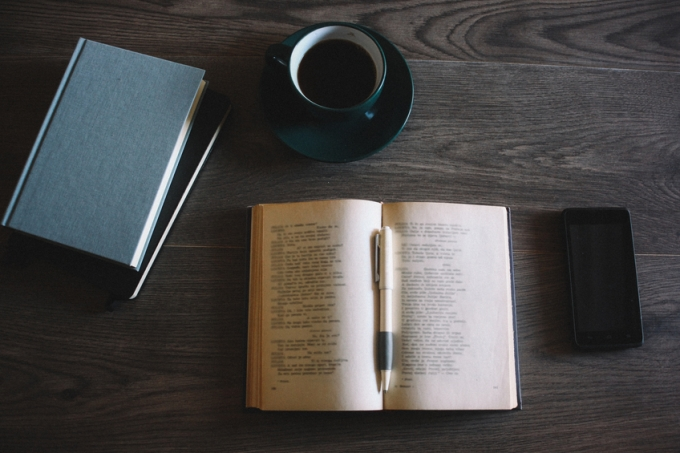 Books, coffee and a smartphone on the wooden background