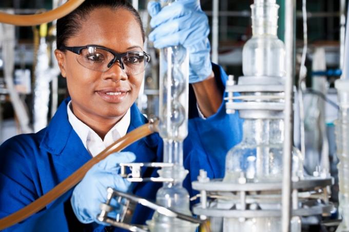 Química trabalhando em equipamento industrial
