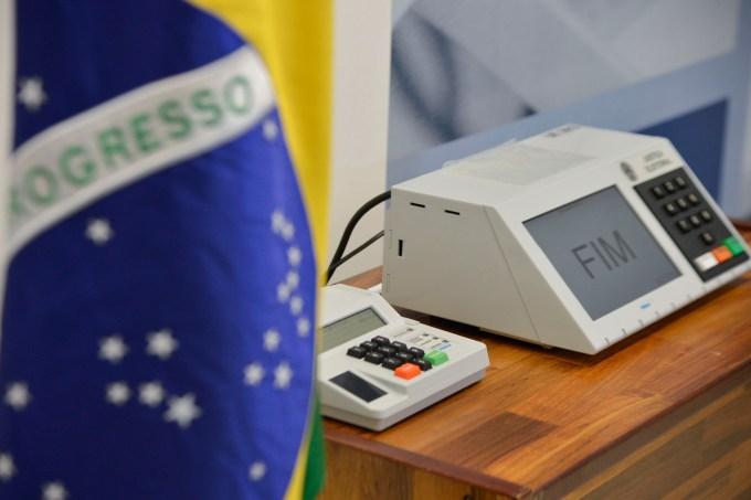 Urna eletrônica e bandeira do Brasil