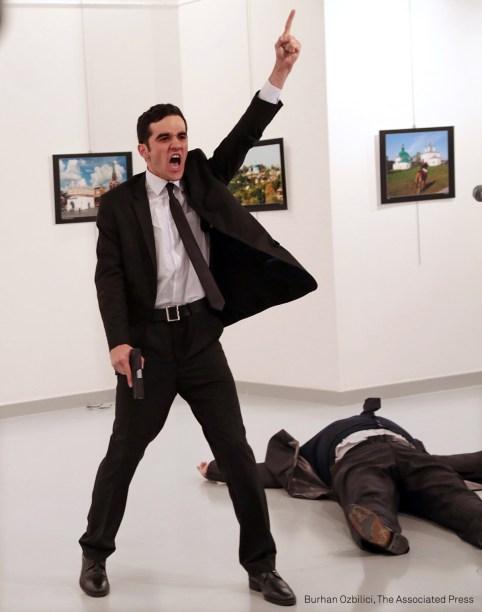 """Mevlüt Mert Altıntaş, um policial de 22 anos, aparece na imagem gritando após atirar contra Andrey Karlov, embaixador russo na Turquia, em uma galeria de arte em Ancara, capital da Turquia, em dezembro de 2016. O embaixador morreu no local. Minutos depois do atentado, o policial foi morto pelas forças de segurança da Turquia. O ataque teria sido um protesto contra a intervenção russa na Síria. Antes de matar o embaixador, o policial gritou: """"não se esqueçam de Aleppo, não se esqueçam da Síria!"""".  (foto: AP Photo/Burhan Ozbilici/World Press Photo 2017)"""