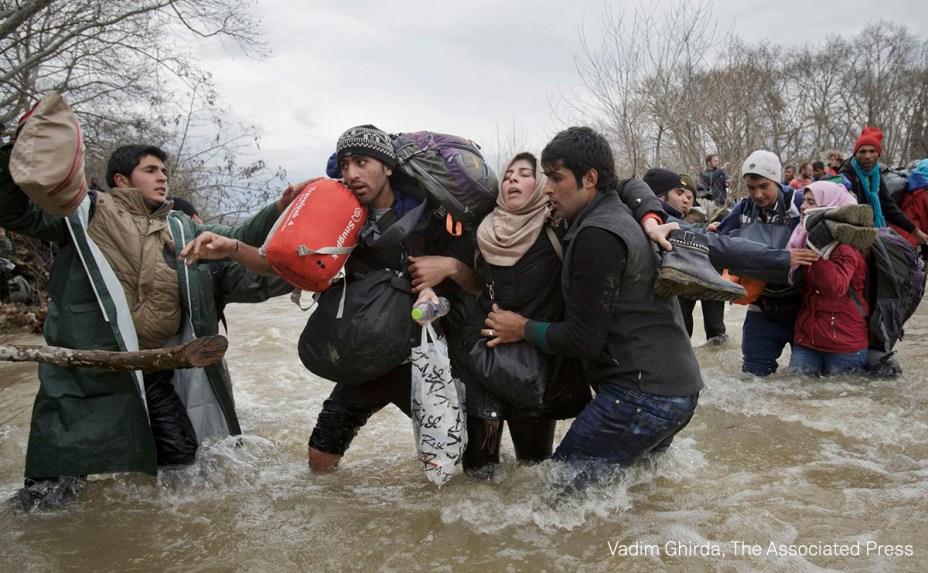"""Uma mulher é carregada por dois homens enquanto cruzam um rio, em março de 2016. São refugiados que abandonaram um campode refugiados na Grécia e tentam chegar à Macedônia. <div id=""""desc-default""""><span>(foto: Vadim Ghirda/World Press Photo 2017)</span></div>"""