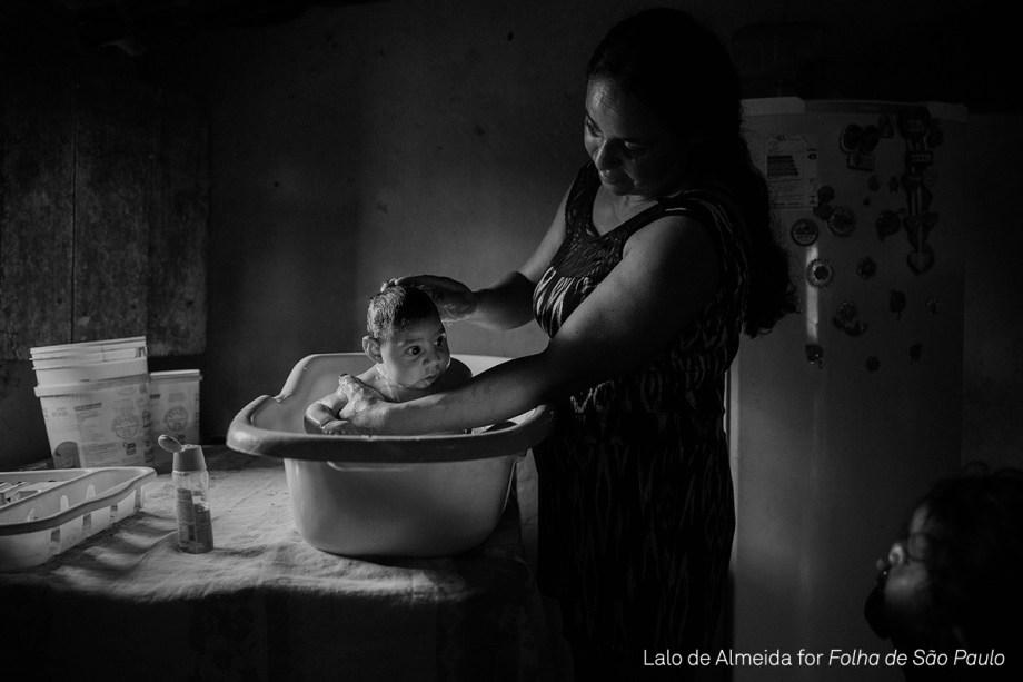"""Adriana Cordeiro Soares, banha seu filho, João Miguel de três meses, em outubro de 2016, na zona rural de<span>São Vicente do Seridó (PB)</span>. O bebê nasceu com microcefalia, provocada pela contaminação da mãe pelo vírus da zika <div class=""""photo-desc"""">(foto: Lalo de Almeida/World Press Photo 2017)</div>"""