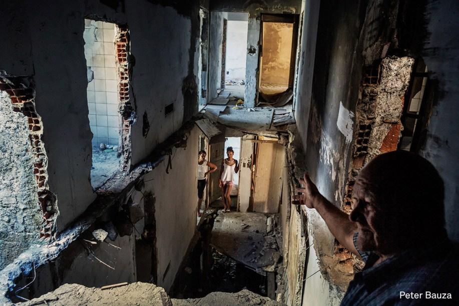 Um pastor mostra o prédio abandonado onde mora, que também é ocupado por outras famílias sem-teto, em julho de 2015.  <span>(foto: Peter Bauza/World Press Photo 2017)</span>
