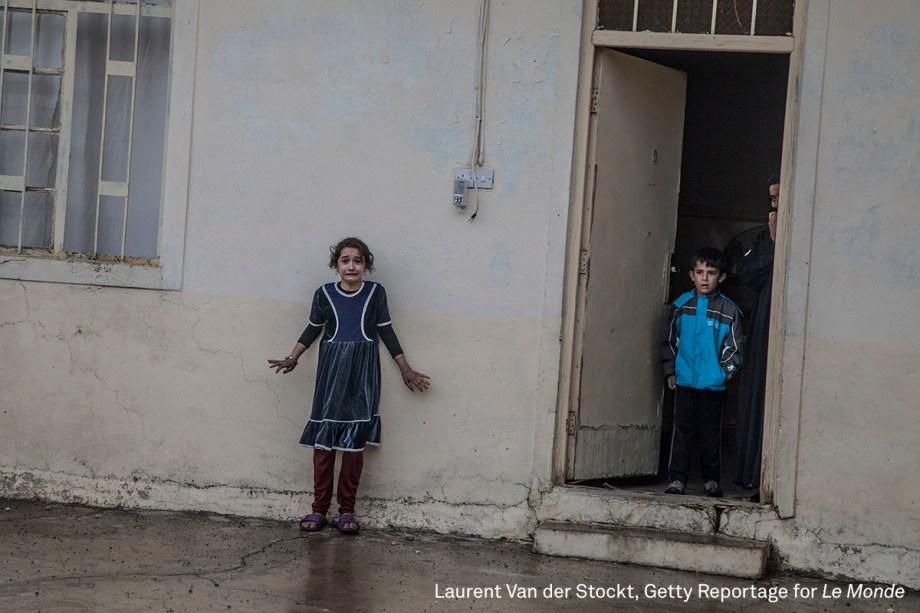"""Garota olha assustada para membros das Forças de Operações Especiais do Iraque, em Mossul, em novembro de 2016. As tropas procuram membros do Estado Islâmico, contra quem travam uma guerra pelo controle da cidade. <div id=""""desc-default""""><span>(foto: Laurent Van der Stockt/World Press Photo 2017)</span></div>"""