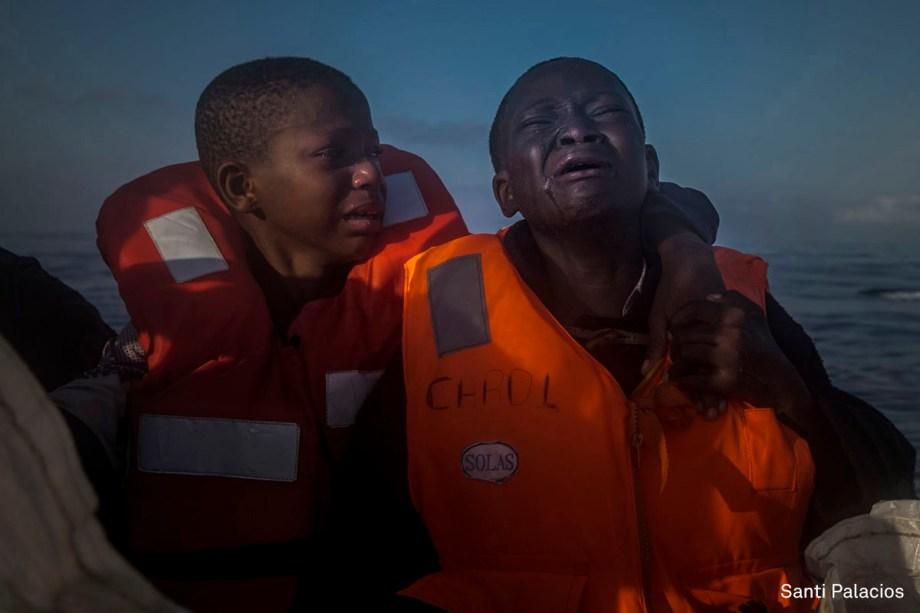 Garota nigeriana chora ao lado de seu irmão após saber que sua mãe morrera na Líbia, em julho de 2016. Eles estão em um barco de resgate após navegar por horas em um bote inflável pelo Mar Mediterrâneo.  <span>(foto: Santi Palacios/World Press Photo 2017)</span>