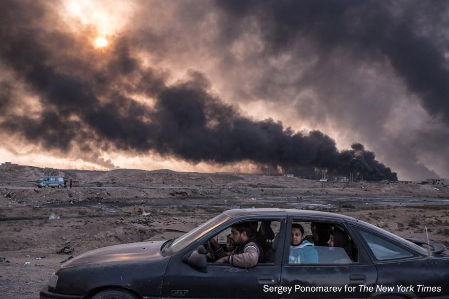"""Família foge de Mossul, a segunda maior cidade do Iraque, enquanto campos de petróleo queimam ao fundo, em novembro de 2016. A cidade, ocupada pelo grupo terrorista Estado Islâmico, é alvo de operações das forças iraquianas para tentar retomar o controle. <div class=""""photo-desc""""><span>(foto: Sergey Ponomarev/World Press Pohto 2017)</span></div>"""
