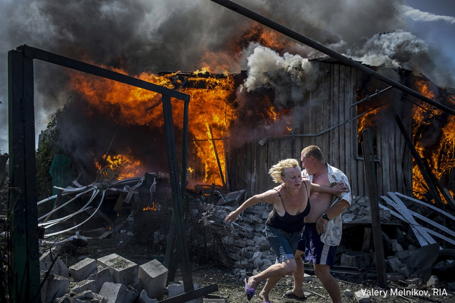 Civis fogem de uma casa em chamas, destruída após um ataque aéreo na região de Donbass, na Ucrânia, em julho de 2014. No período, o leste do país era palco de confrontos entre separatistas, apoiados pela Rússia, e as forças da Ucrânia.  <span>(foto Valery Melnikov/World Press Photo 2017)</span>