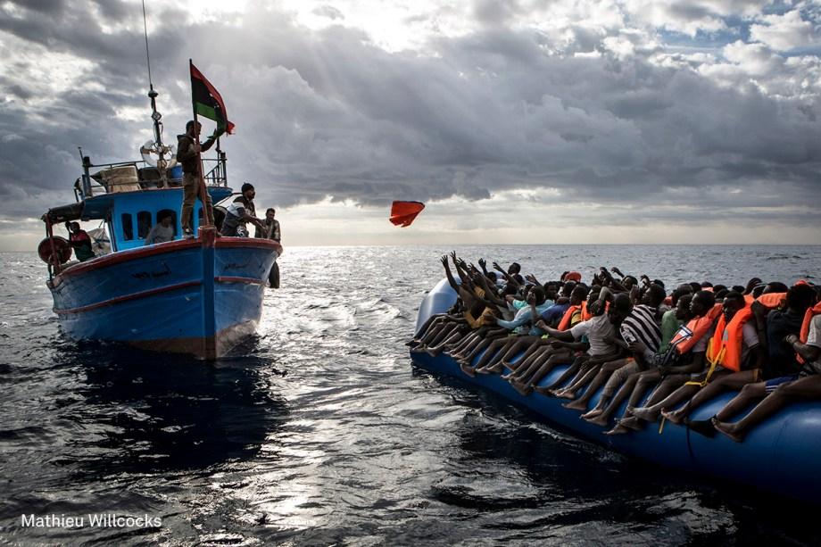 Pescador líbio joga um colete salva-vidas em direção a um bote inflável lotado de imigrantes, no Mar Mediterrâneo, em novembro de 2016.  (foto: Mathieu Willcocks/World Press Photo)