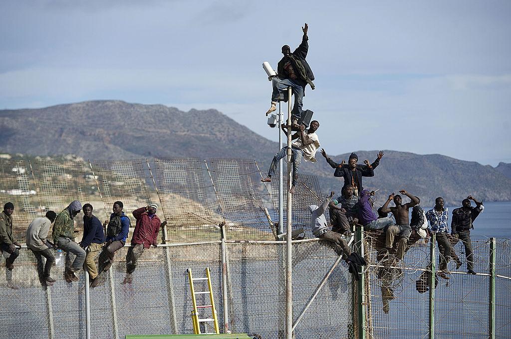 Imigrantes africanos escalam a cerca que separa o Marrocos do enclave espanhol de Melilla