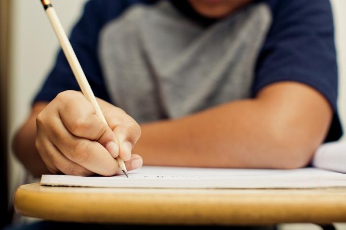 Aluno escrevendo com lápis em uma carteira da escola