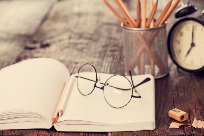 Caderno, lápis, óculos, apontador, material escolar